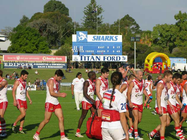 The blue and white scoreboard tells a red and white story at half time in the derby. Photo by Les Everett.