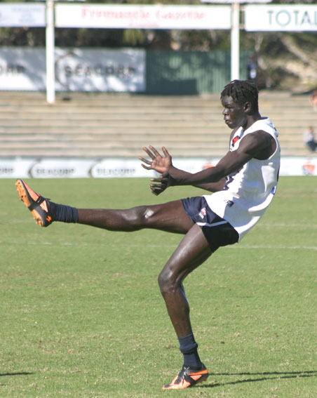 Vic Country ruckman Gach Nyuon kicks for goal. The kick was a shocker but somehow made its way between the big sticks. Photo by Les Everett